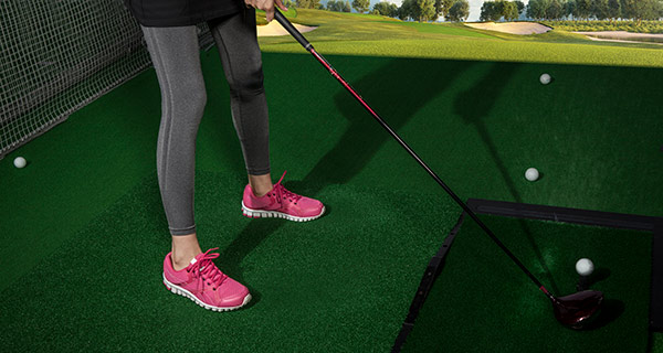golf simulator in home and women teeing up