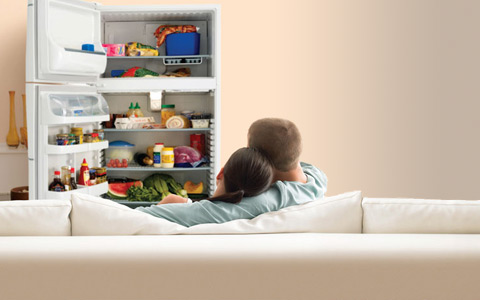couple sitting on couch looking at refrigerator where tv should be