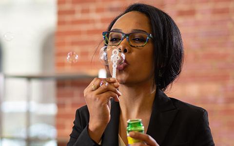 woman blowing bubbles for eyewear store
