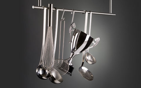 close up of silver cup award hanging with other kitchen utensils