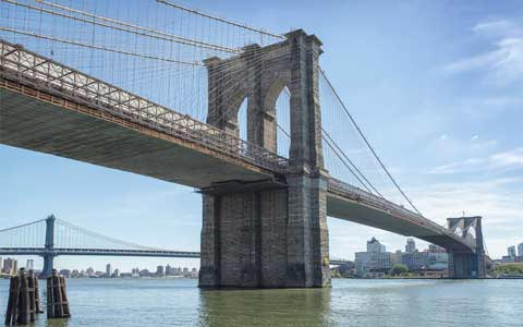 Dramatic view of the Brooklyn Bridge form the water's level