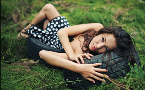 beautiful woman in formal dress lying on old tire in field