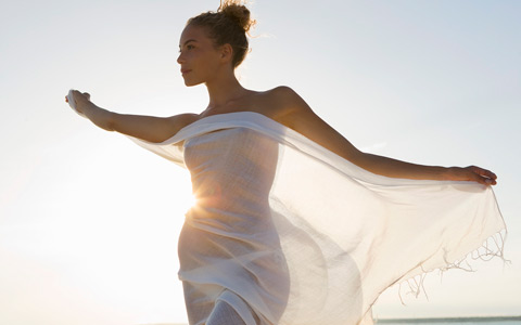 nude woman on the beach holding large sheet of gauze over her body