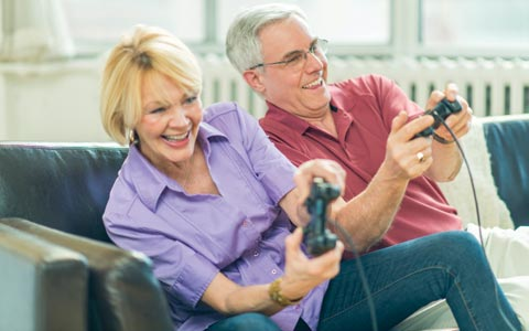 retired couple on couch playing video game by SEO agency Sevell