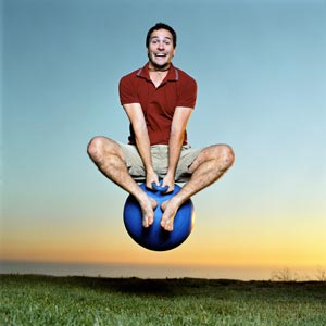 man bouncing on child's large rubber ball looking very excited