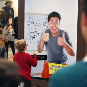 interactive kiosk of guy playing Pictionary with shoppers