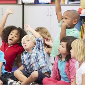 kids in kindergarten enthusiastically raising their hands