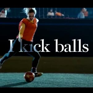 Young woman kicking soccar ball with the words I kick balls over her photo
