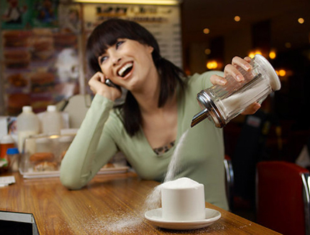 woman not paying attention and overpouring sugar in her coffee