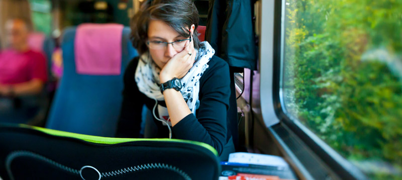 woman working on computer on train creating short-form content